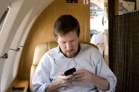 Business Executive on Corporate Jet Working on Blackberry