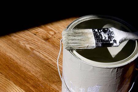 Paint Bucket on Hardwood Floor with Paintbrush