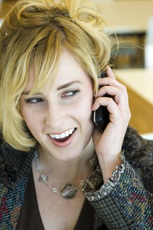 Young Blonde Caucasian Woman Answering Phone in Office photo