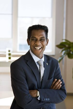 Indian Business Man Laughing with Arms Folded Indoors Stock Photo