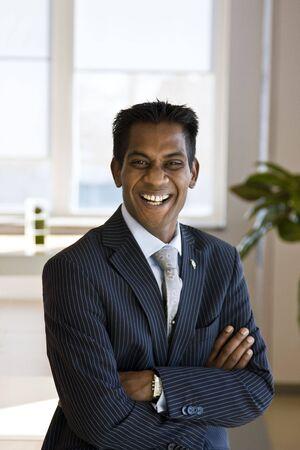 Indiase zaken Man lachen met armen gevouwen binnenshuis