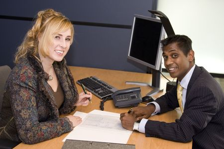 Indian Business Man and Caucasian Woman Signing a Contract photo