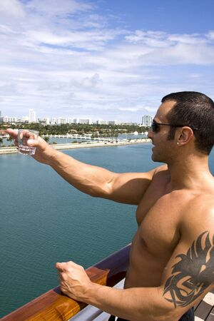 italian sea: Young Muscular Male on Ship Deck Pointing at Ocean