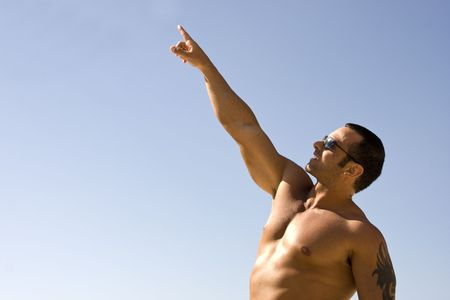 Young Muscular Male Pointing at Sky with Blue Background