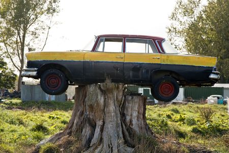 Old Car Trapped and Balancing on Tree Stump