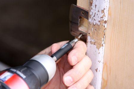 動力工具とドアを修理する人