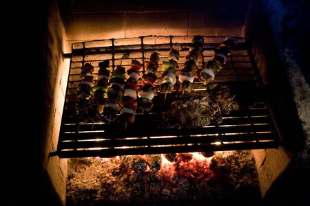 Shish Kabobs and Steak on Outdoor Grill at Night Фото со стока