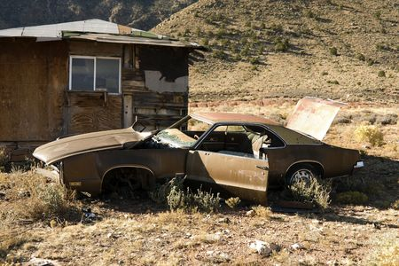 Abandoned Junk Car in Desert next to House photo
