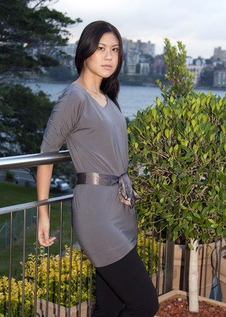 Young Asian Woman Standing Outdoors Against Fence
