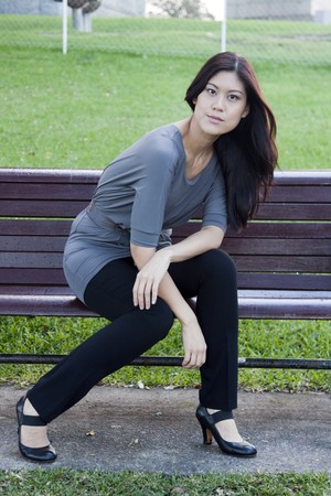 Young Asian Woman Sitting Down on Park Bench
