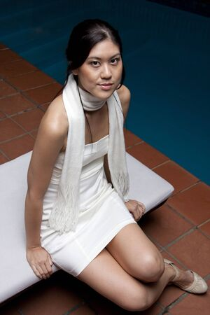 Young Asian Woman Sitting Down Near Pool Stock Photo