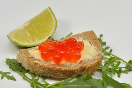 Fresh Salmon Raw Roe Sandwich (Red Caviar) on Rucola Leaves and Slice of Lime, isolated on white background