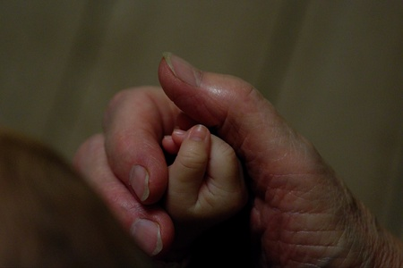 grandkids: Detail as grandmother is holding grandchilds hand. Stock Photo