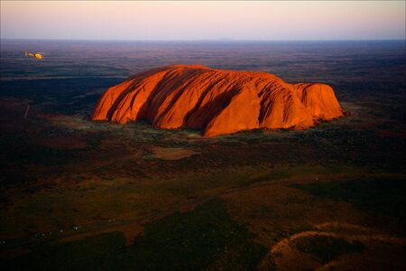 Uluru. Orange Uluru in bright beams of the sunset sun.