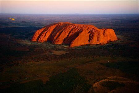 ayers: Uluru. Orange Uluru in bright beams of the sunset sun.