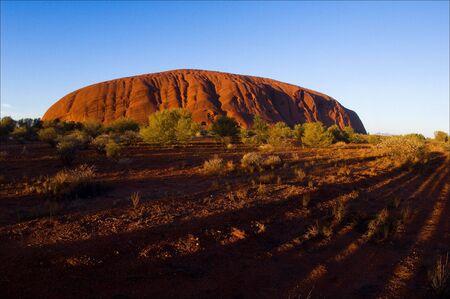 Uluru. A monolith of Uluru on rising in bright orange beams of the sun, long shades.
