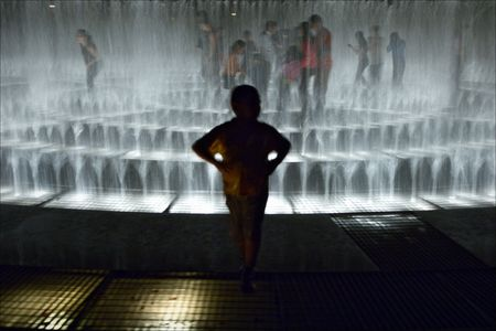 At a fountain. A silhouette of the boy against a fountain in which streams children play. photo