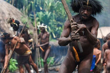 The Papuan banishes from the village, swinging a stick.