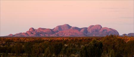 australian landscape: Colourful beams of a rising sun have lit up Kata Tjuta. Stock Photo