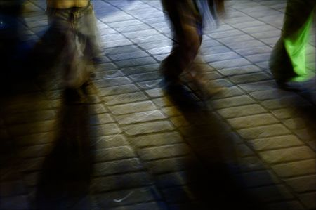 Feet march on a stone blocks in city twilight. photo