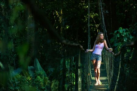The girl on the pendant bridge in wood. The beautiful young girl costs on the pendant bridge in green wood. photo