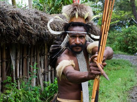 The warrior of Dani Dugum tribe with an bow and an arrow aims in the photographer. Indonesia. 25 July 2009.