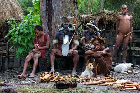 aborigen: Los nativos de Nueva Guinea Dani de una tribu sentarse en un banco en la village.Indonesia. 25 De julio de 2009.