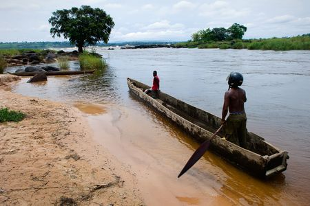 Two men float in a wooden boat on the river Congo