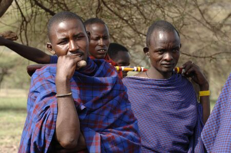 Africa. Tanzania. On March, 5th 2009 . Maasai village. A group portrait maasai men. Savanna. A shining sun.