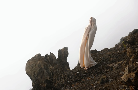 The girl shrouded in a cloud, it is high in mountains, early in the morning. photo