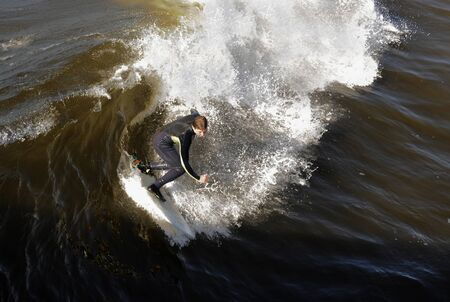 Surfer gets up on a wave. The wave twists with foam and splashes. photo