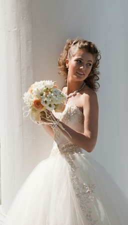 The bride with a bouquet. The bride in a wedding dress with a bouquet on the white.