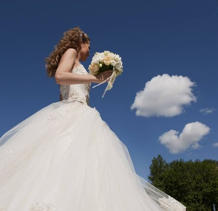 The bride with a bouquet and the sky. The bride in a wedding dress with a bouquet with clouds. photo