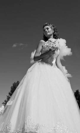 The bride with a bouquet and the sky. The bride in a wedding dress with a bouquet with clouds. Black and white photo. photo