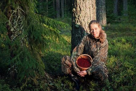 Young Woman picking ripe cranberries. Vaccinium vitis idaea photo