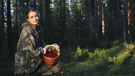 Young Woman picking ripe cowberies.  photo