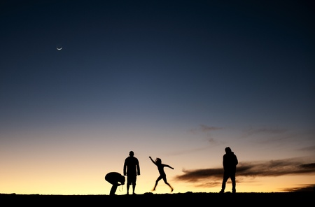 Silhouette of people and photographers on mountain at dawn. Silhouettes of people against the night sky. After a decline. Stock Photo