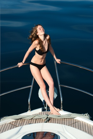 Girl relaxing on a yacht.Young woman is sunning on an motoryacht photo