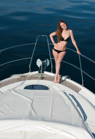 hot legs: Girl relaxing on a yacht.Young woman is sunning on an motoryacht