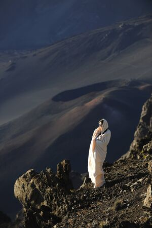 The girl at craters of Haleakala. Early morning, a smoke, wrapped up in white the girl in rising sun beams costs at edge of breakage against craters. photo