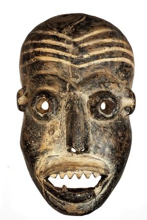 maschera tribale: Legno intagliato maschera africana tribale, in legno scuro con la faccia dipinta. Isolato su sfondo nero. Congo, Africa Archivio Fotografico