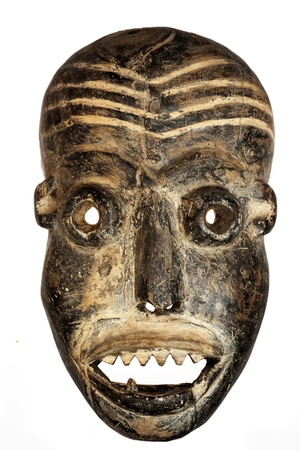 african warriors: Wooden carved African tribal mask, dark wood with painted face. Isolated on black  background. Congo, Africa Stock Photo