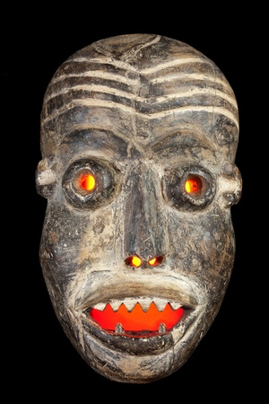 artifact: Wooden carved African tribal mask, dark wood with painted face  Isolated on black  background  Congo, Africa