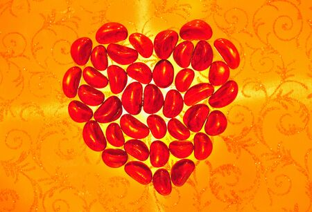 The red shone heart from glass parts on an  yellow openwork background photo