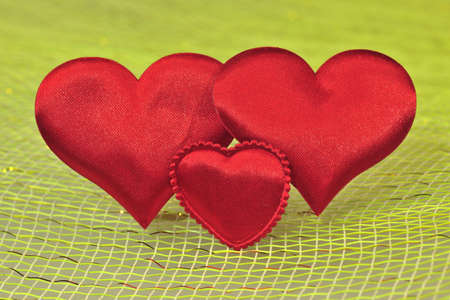 Three Silk red hearts  on a light background. Stock Photo - 12193288