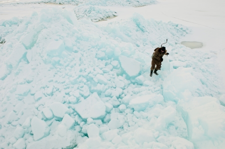 The fisherman clambering on ice blocks  photo