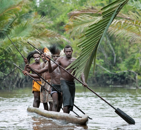 INDONESIA, IRIAN JAYA, ASMAT PROVINCE, JOW VILLAGE - JUNY 28:  Asmat men paddling in their dugout canoe. Canoe war ceremony of Asmat people. Headhunters of a tribe of Asmat show traditional and national customs, dresses, the weapon and boats. New Guinea I