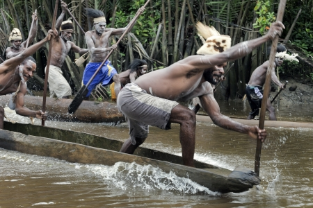 neckless: INDONESIA, NEW GUINEA, ASMAT PROVINCE, JOW VILLAGE - JUNY 28: The Asmat Warriors  with a spear - oars float on the dugout canoes, national dresses, neckless, the weapons, painting. New Guinea, Indonesia. June 28 2012 Editorial