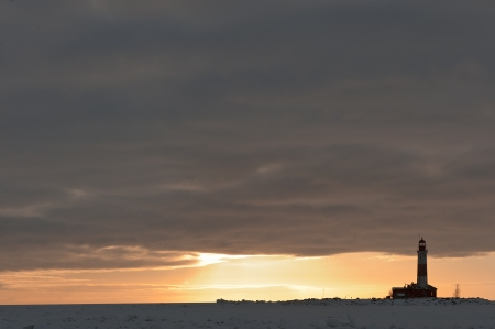 Winter Lighthouse at sunset  The Lighthouse island in the winter on the Ladoga Lake  Russia  photo