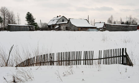 Fence at the village in a snow-covered field  Winter  Russia photo